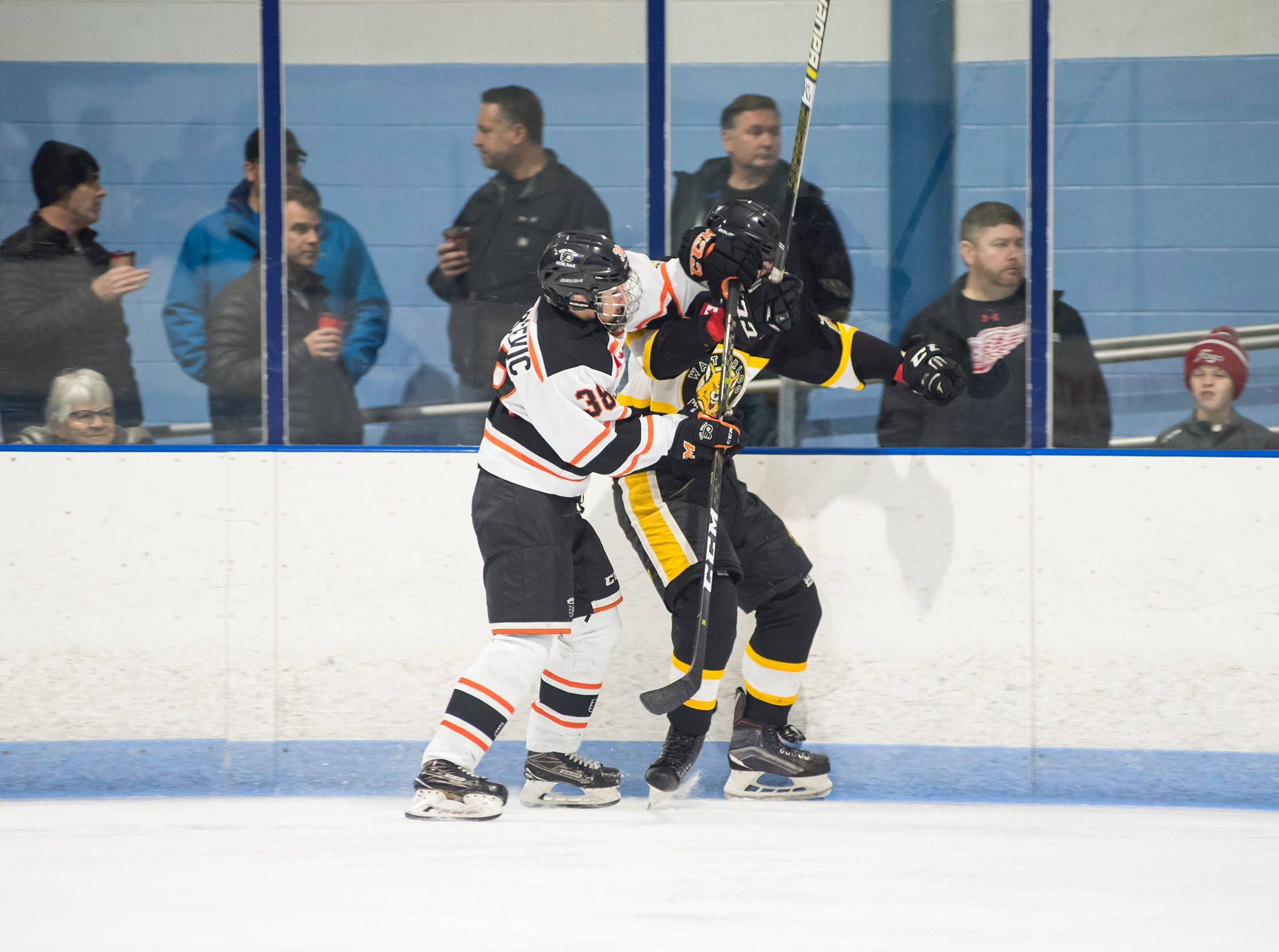 Don Mills Flyers forward Michael Starcevic (36) checks Waterloo Wolves defenseman Macgregor Roy into the wall during their BAAA-A Silver Stick Finals match Friday, Jan. 4, 2019 at Glacier Pointe Ice Complex.