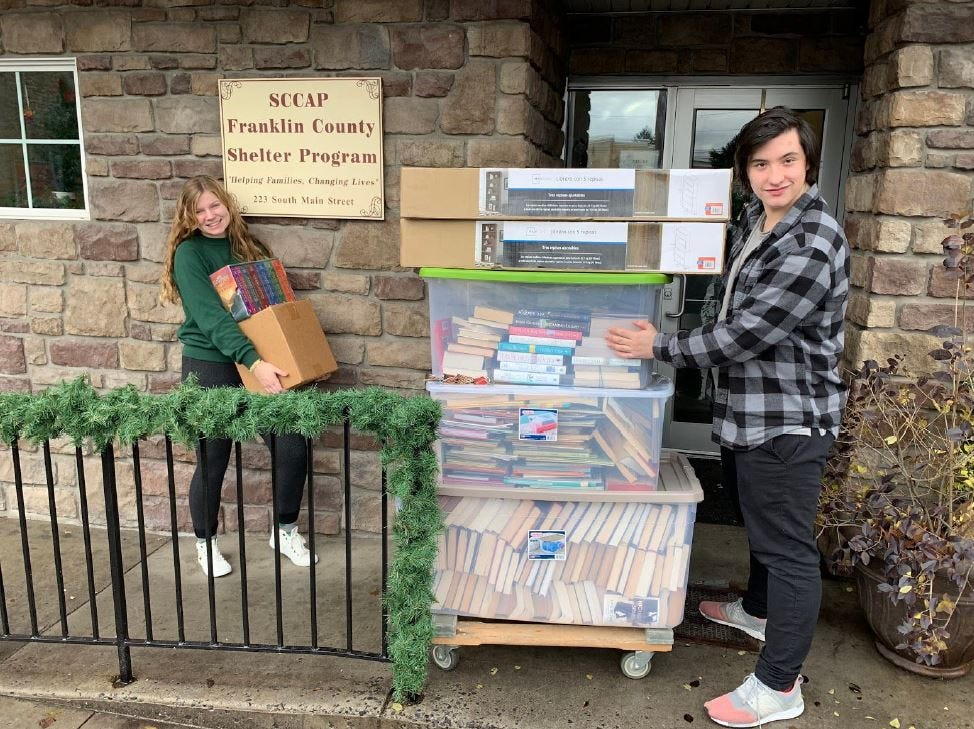 Madison Mellinger and Kyle Chastulik carry donated books and bookshelves - including the full Harry Potter series - into the Southcentral Community Action Program Franklin County Homeless Shelter on South Main Street, Chambersburg. Kelton Chastulik, Chambersburg, hosted a book drive over the holidays to benefit libraries at homeless shelters. The goal was 200 books, but 4,500 were raised.