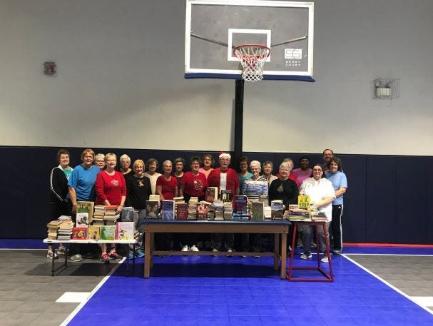 "Chambersburg Results Fitness ""Silver N Fit"" crew stand next to their donation of books. Kelton Chastulik, Chambersburg, hosted a book drive over the holidays to benefit libraries at homeless shelters and other facilities."