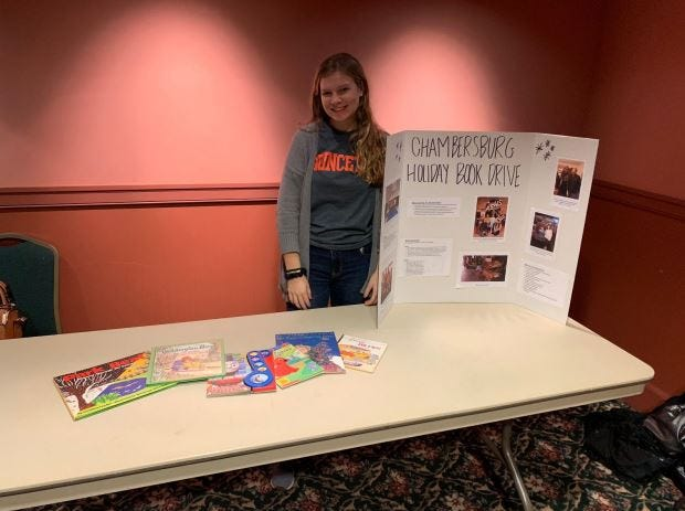 Madison Mellinger standing next to a posterboard of photos while we tabled at the Capitol Theatre during their shows of It's a Wonderful Life and the Nutcracker. Kelton Chastulik, Chambersburg, hosted a book drive over the holidays to benefit libraries at homeless shelters.. The goal was 200 books, but 4,500 were raised.