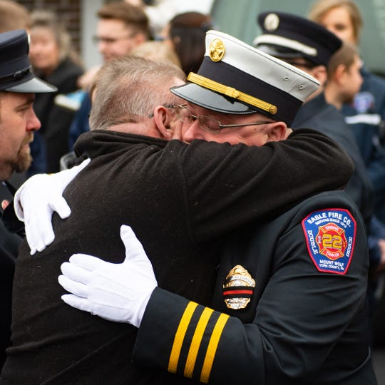 Robert Kohler Jr. hugs close friends after his father was brought out to the ambulance for one last ride, January 4, 2018.