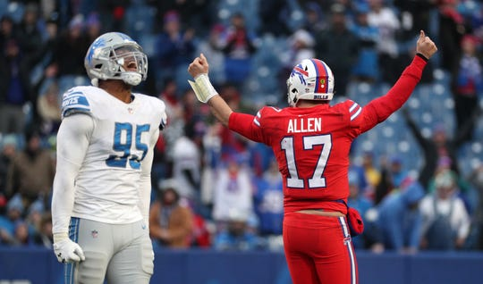 Bills quarterback Josh Allen celebrates near Lions defensive end Romeo Okwar,  after his quarterback sneak gained a first down and allowed Buffalo to run out the clock in a 14-13 win last season