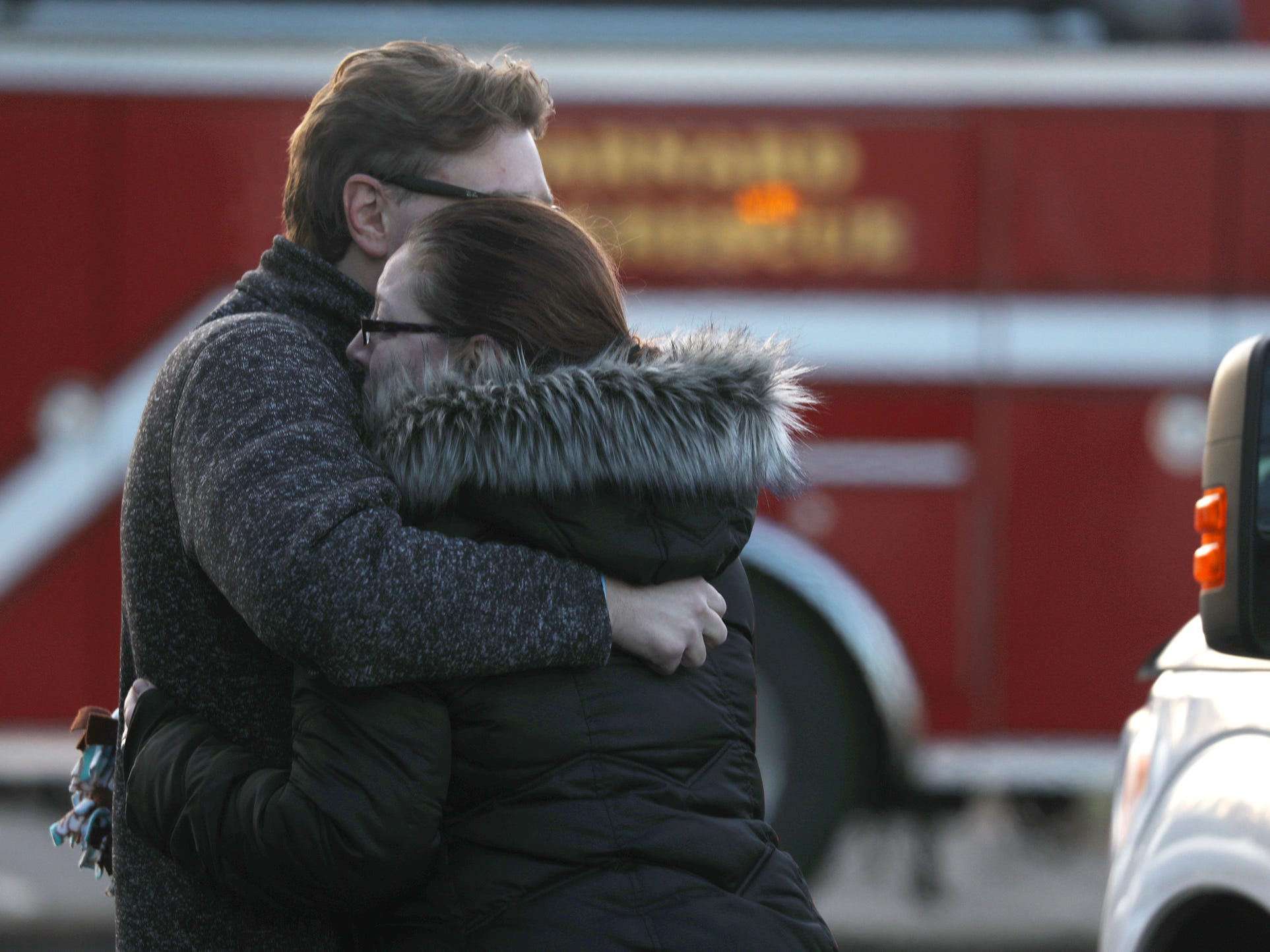 A woman is comforted at the scene of the fire where a woman was found dead in a townhouse on Pond View Heights.