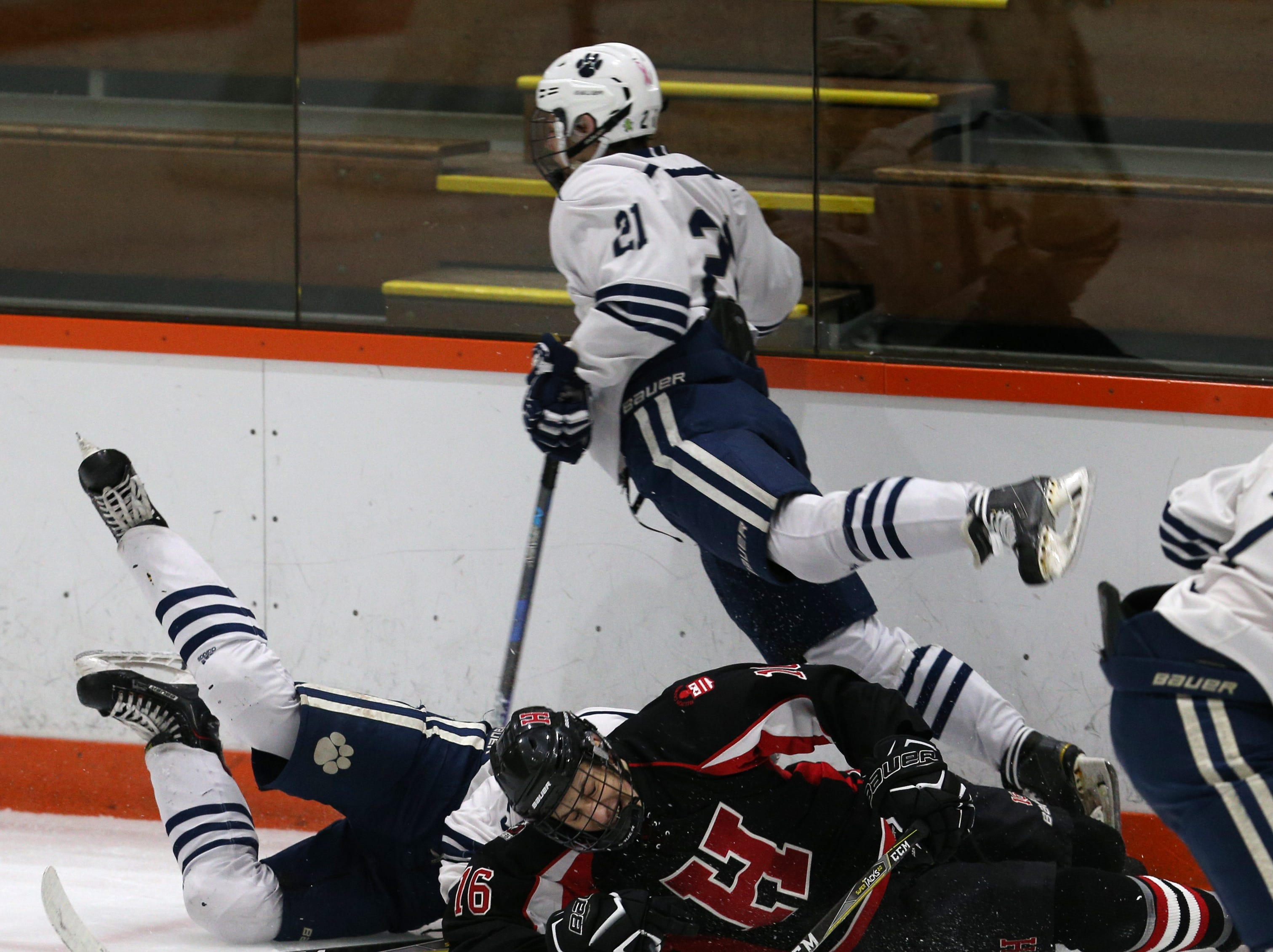 Hilton's Zach Fichtner (16) is taken out by Pittsford along the boards.