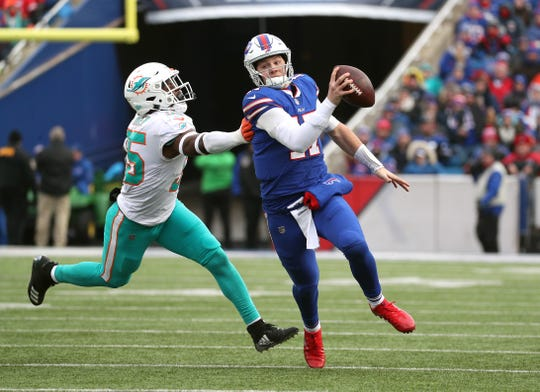 Bills quarterback Josh Allen  runs away from a tackle by Miami's Jerome Baker. Allen rushed for 95 yards and two touchdowns in a 42-17 win.