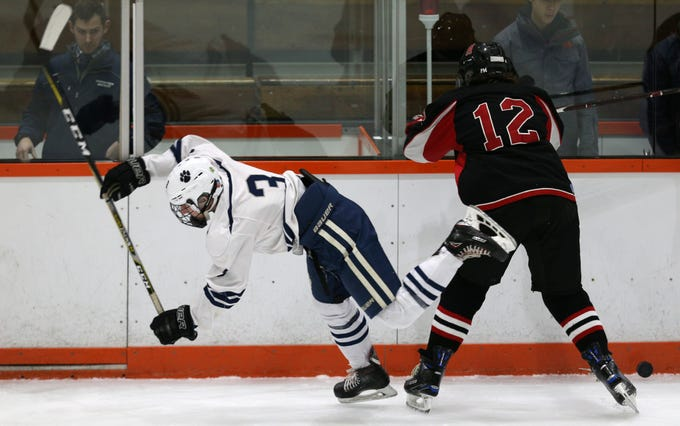Pittsford's Jack Peterson (3) and Hilton's Tyler Koster (12) battle for the puck.