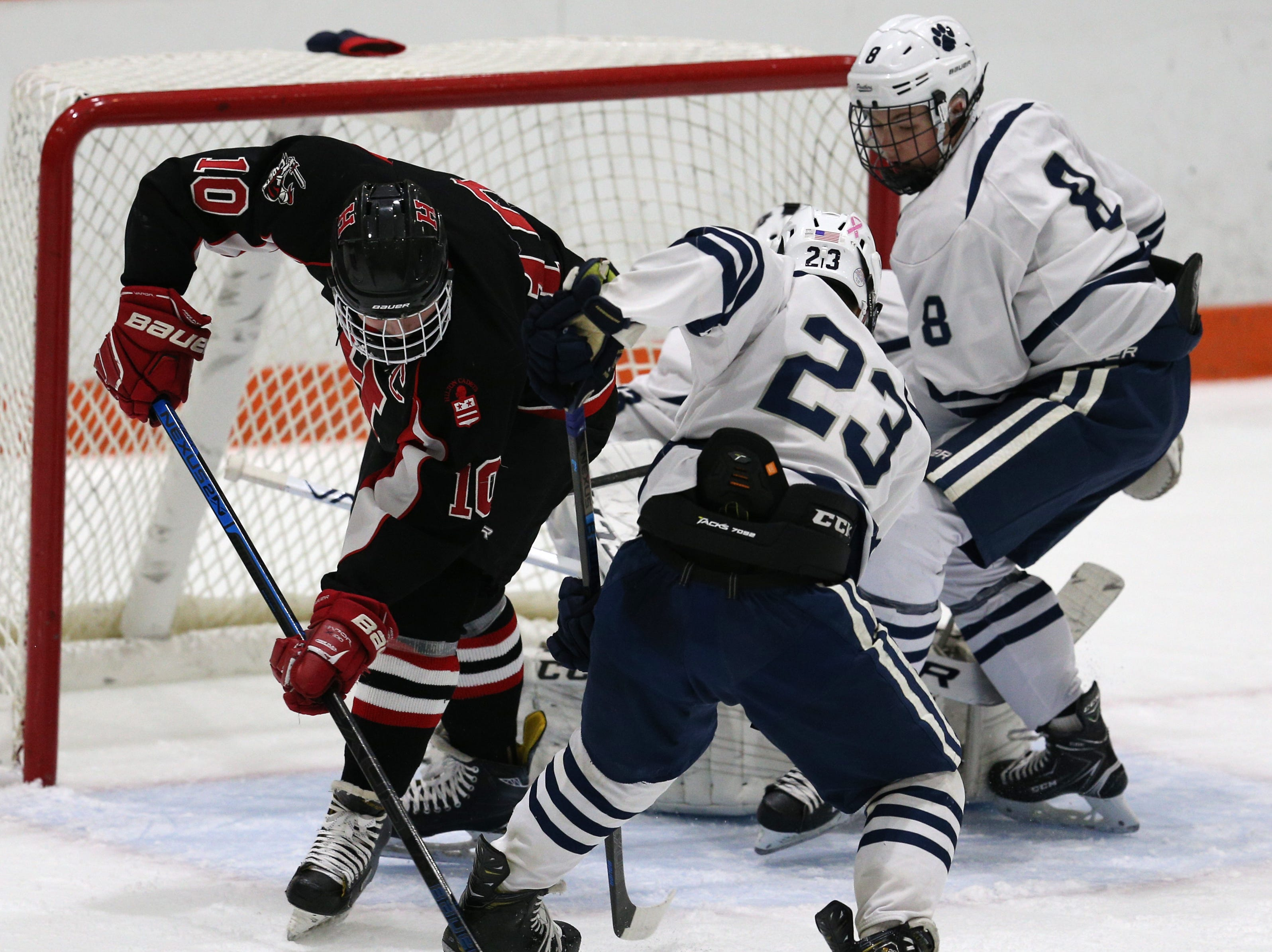 Hilton's Nate Higgins (10) and Pittsford's Brian Judge (23) battle for the puck in front of the Pittsford net.