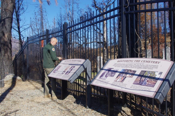 Shasta State Historic Park Interpreter Jonathan Sutliff opens the gate to the Catholic Cemetery at the park. Many of the headstones at the park were damaged during the Carr Fire and had to be cleaned to prevent long-term damage.