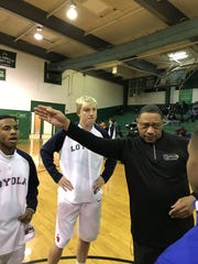 Loyola's Deven Melancon listens to instructions from local basketball official Mike Greene.