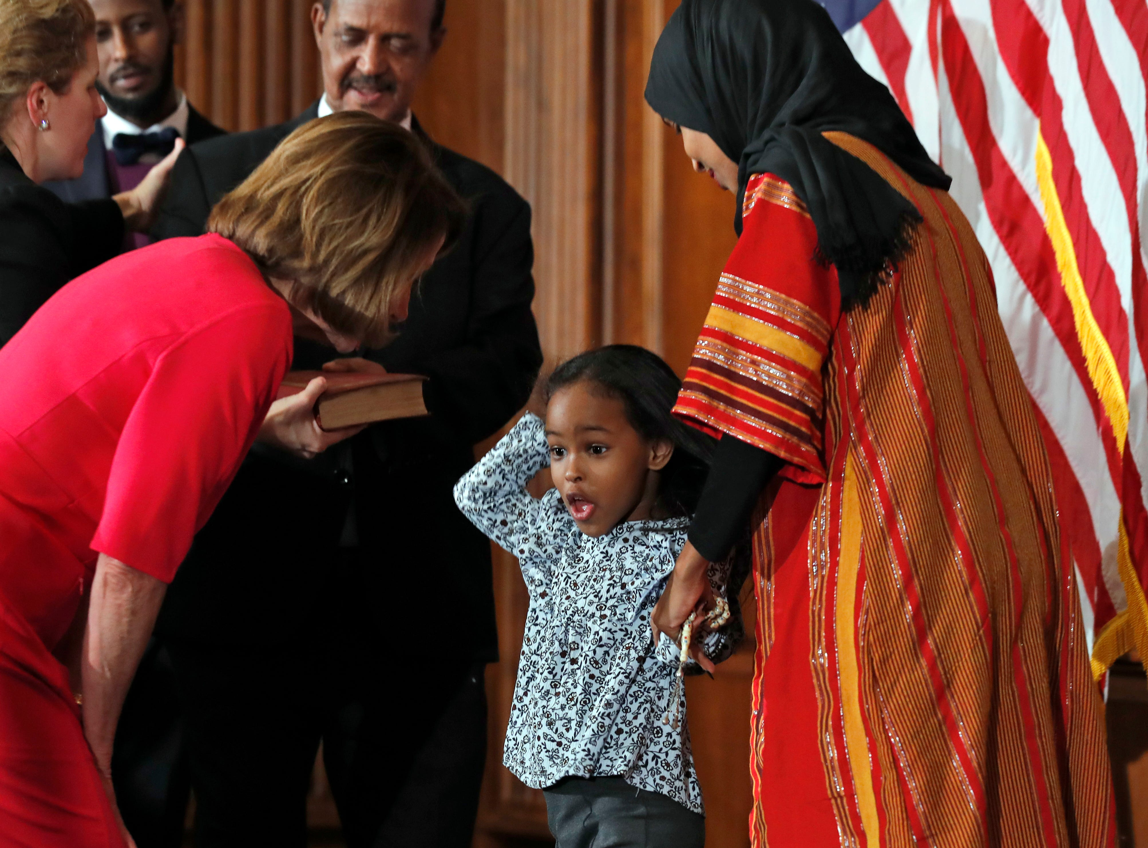 House Speaker Nancy Pelosi of Calif., left, greets a child with Rep. Ilhan Omar, D-Minn., during a ceremonial swearing-in on Capitol Hill, Thursday, Jan. 3, 2019 in Washington during the opening session of the 116th Congress.. (AP Photo/Alex Brandon)