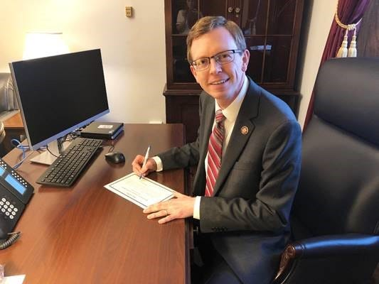 Representative Dusty Johnson signs his official oath of office.