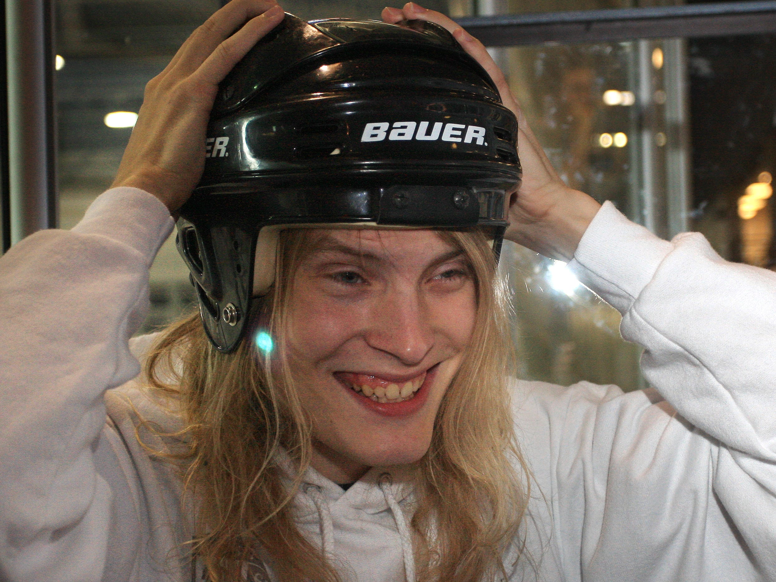 Drury freshman Taylor Smith puts on helmet to join his first-time broomball at Mediacom Ice Park.
