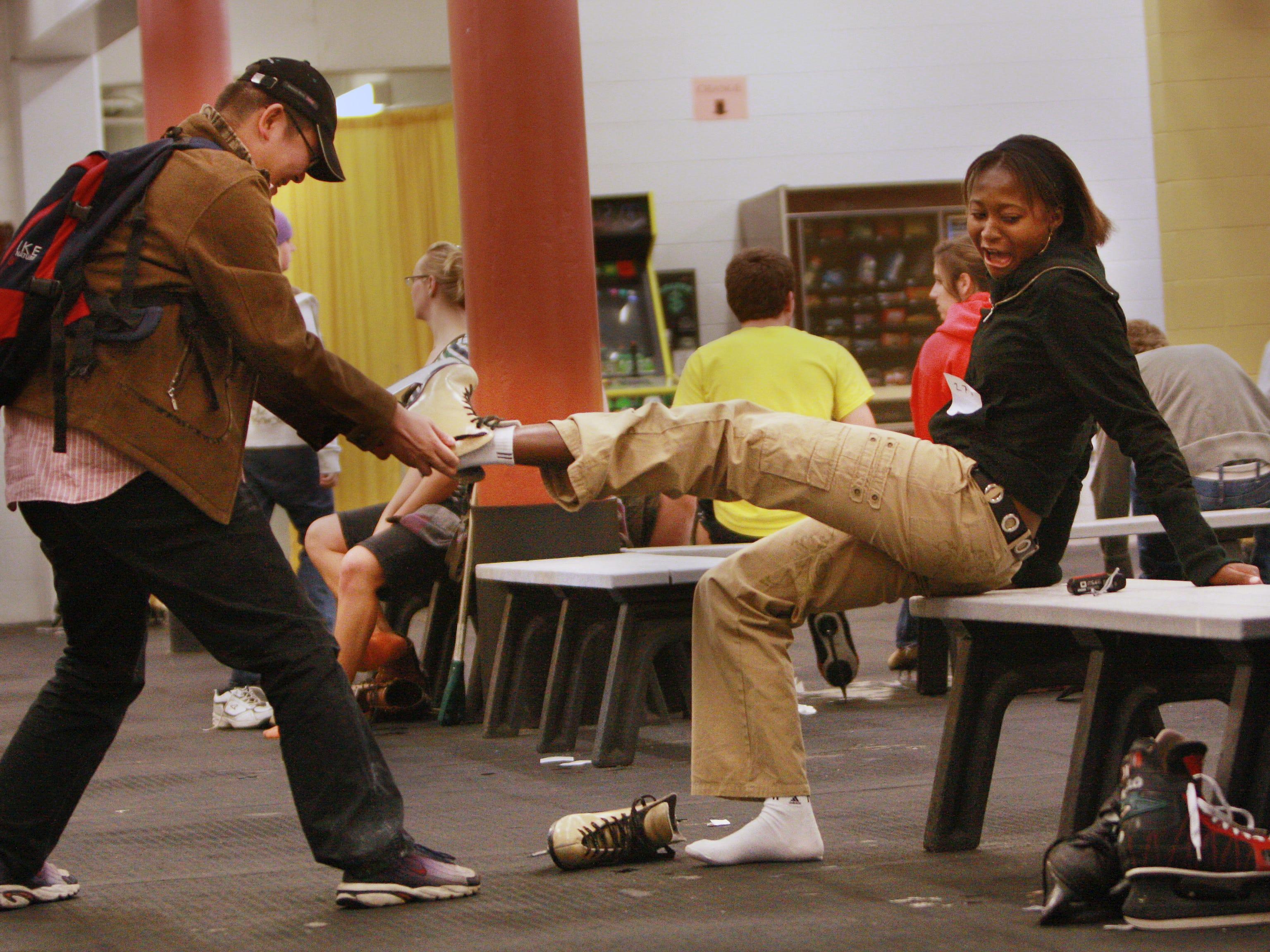 Drury freshman Swensen Xu helps Pelagie Gamo take off her iceskate shoes at Mediacom Ice Park.