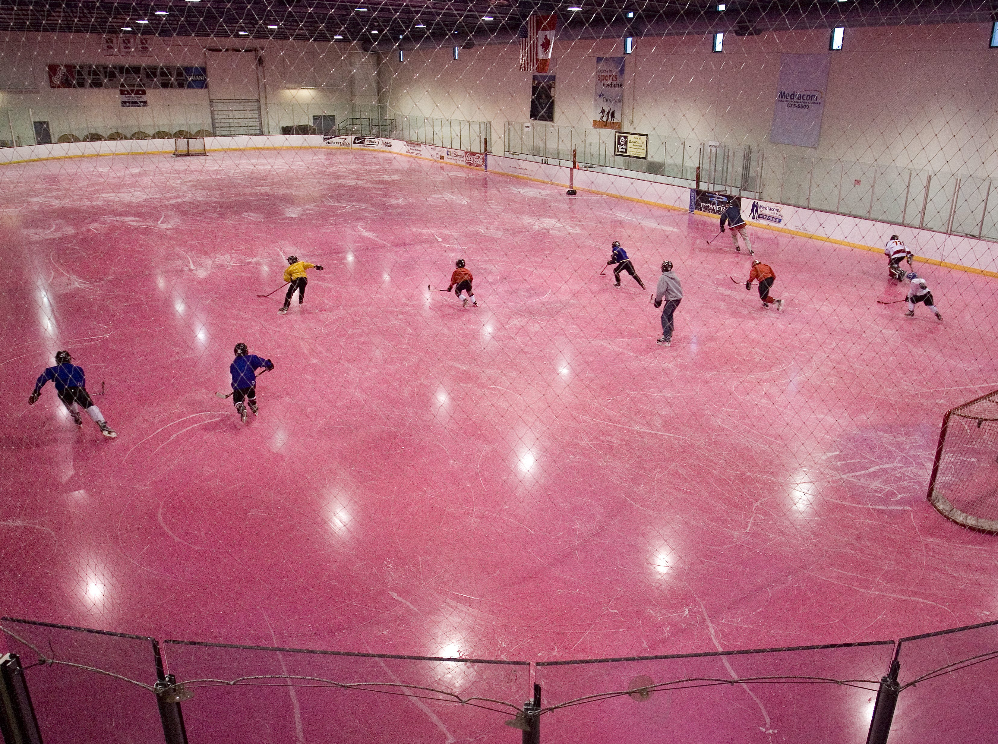 A youth hockey team practice on one of the ice rinks at the Mediacom Ice Park which has been painted pink for breast cancer awareness month.  The ice is made pink by scraping off about an inch of ice with a Zamboni, then hand painting the pink layer, ice is then added back over the top of it.