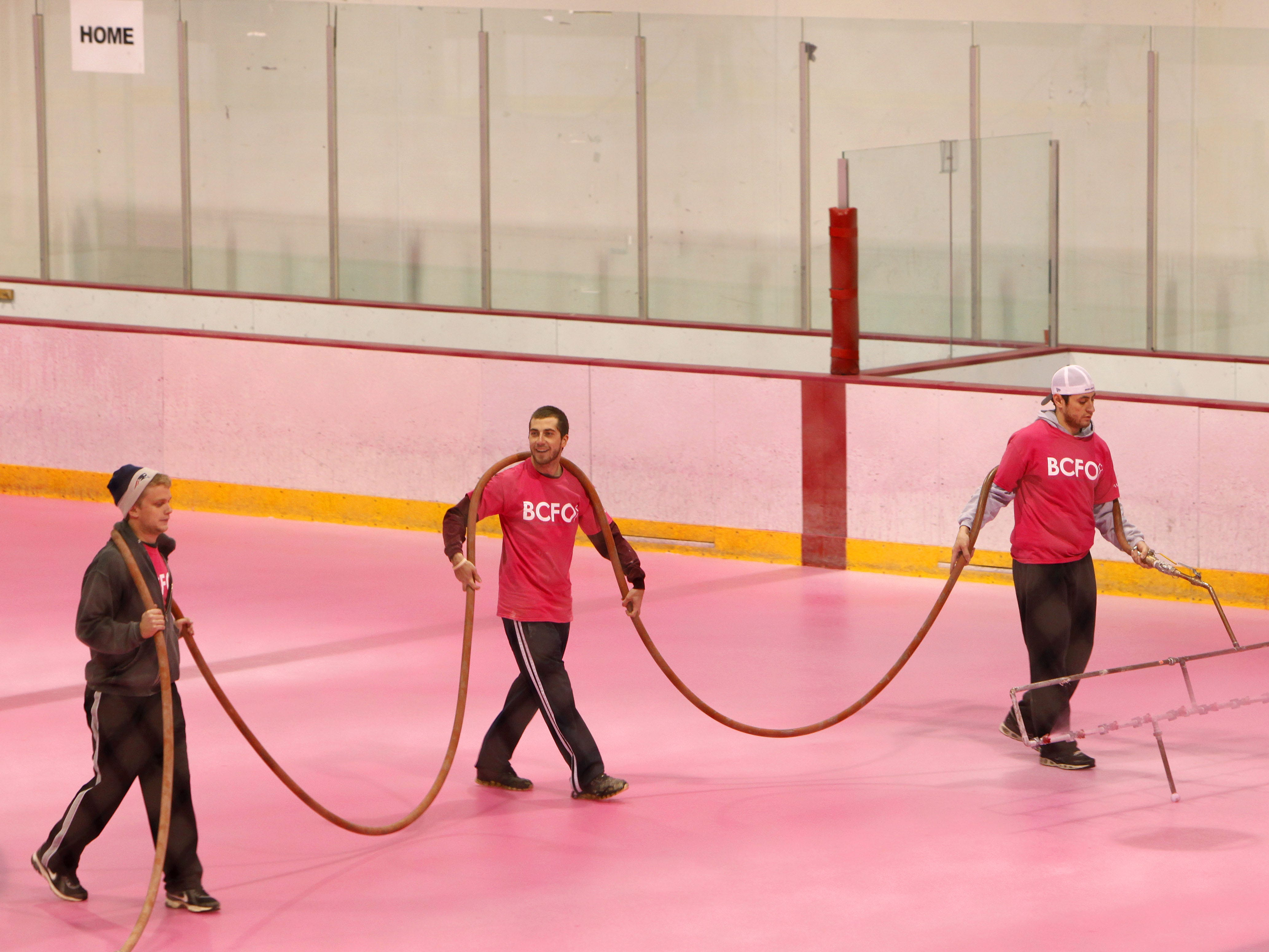 Using a specialized mister, Miguel Franco (right), a manager at the Mediacom Ice Park, paints the ice pink to raise awareness for breast cancer.