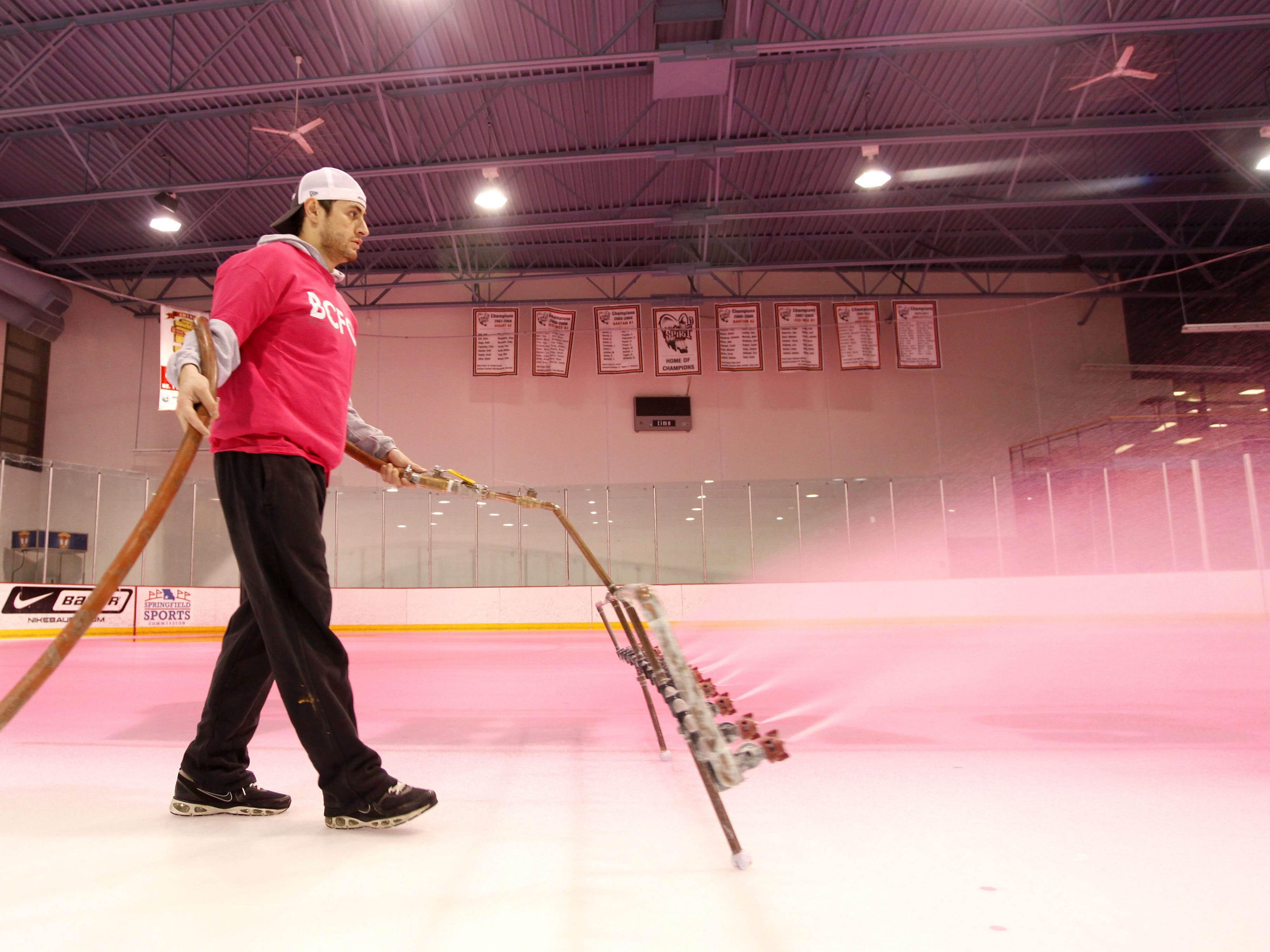 Using a specialized mister, Miguel Franco, a manager at the Mediacom Ice Park, paints the ice pink to raise awareness for breast cancer.