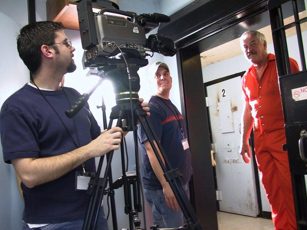 "Brandon Kerr and Chris Nagle set up a shot of Byrne Blackwood (dressed in character as Joe Keegan) in a jail cell during filming of ""Pandoras Box,"" part of a 2002 film festival at what is now Missouri State University."