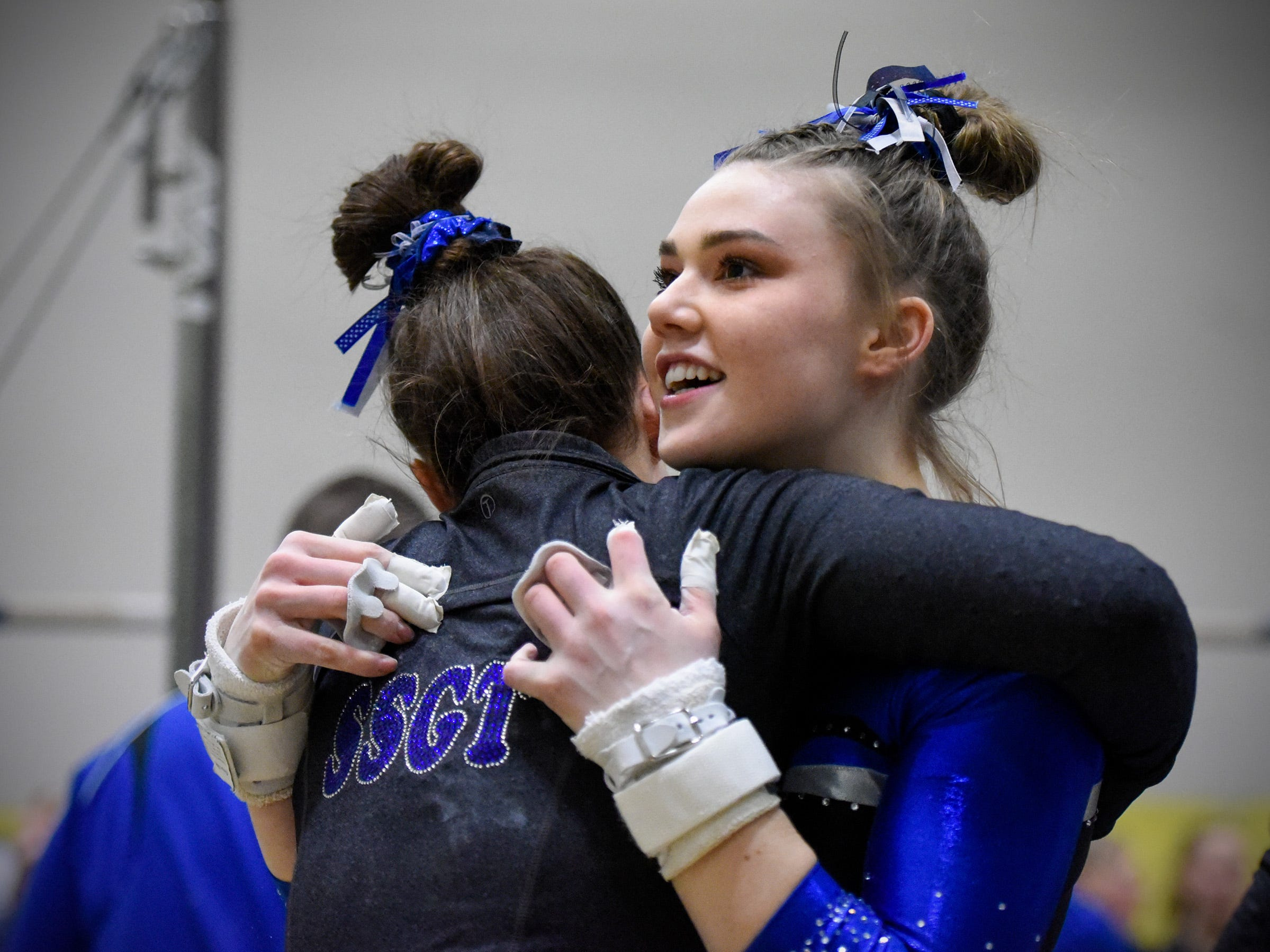 Sartell's Abigail Weber gets a hug from a teammate after her bar routine Thursday, Jan. 3, at the Sauk Rapids-Rice High School.