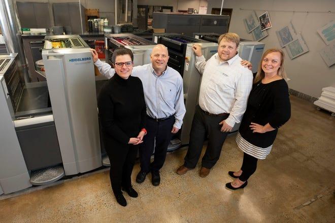 Kristin Rothstein, Kurt Rothstein, Peter and LeRae Rengel gather around the Heidelberg Speedmaster at Rengel Printing.