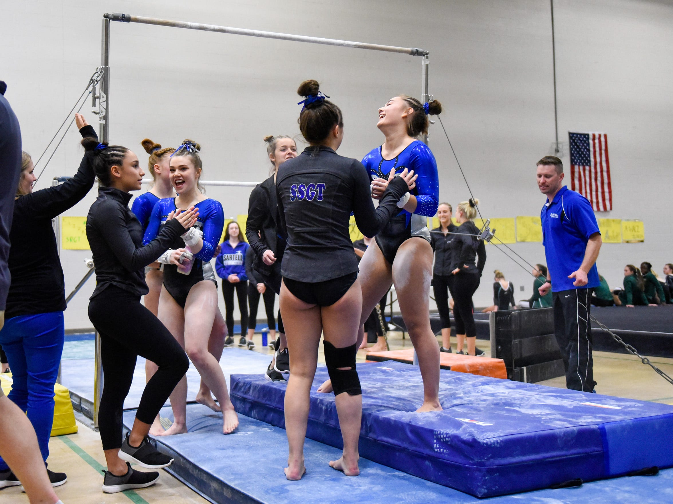 Sartell's Carley Yang is met by teammates after competing on the bars Thursday, Jan. 3, at the Sauk Rapids-Rice High School.