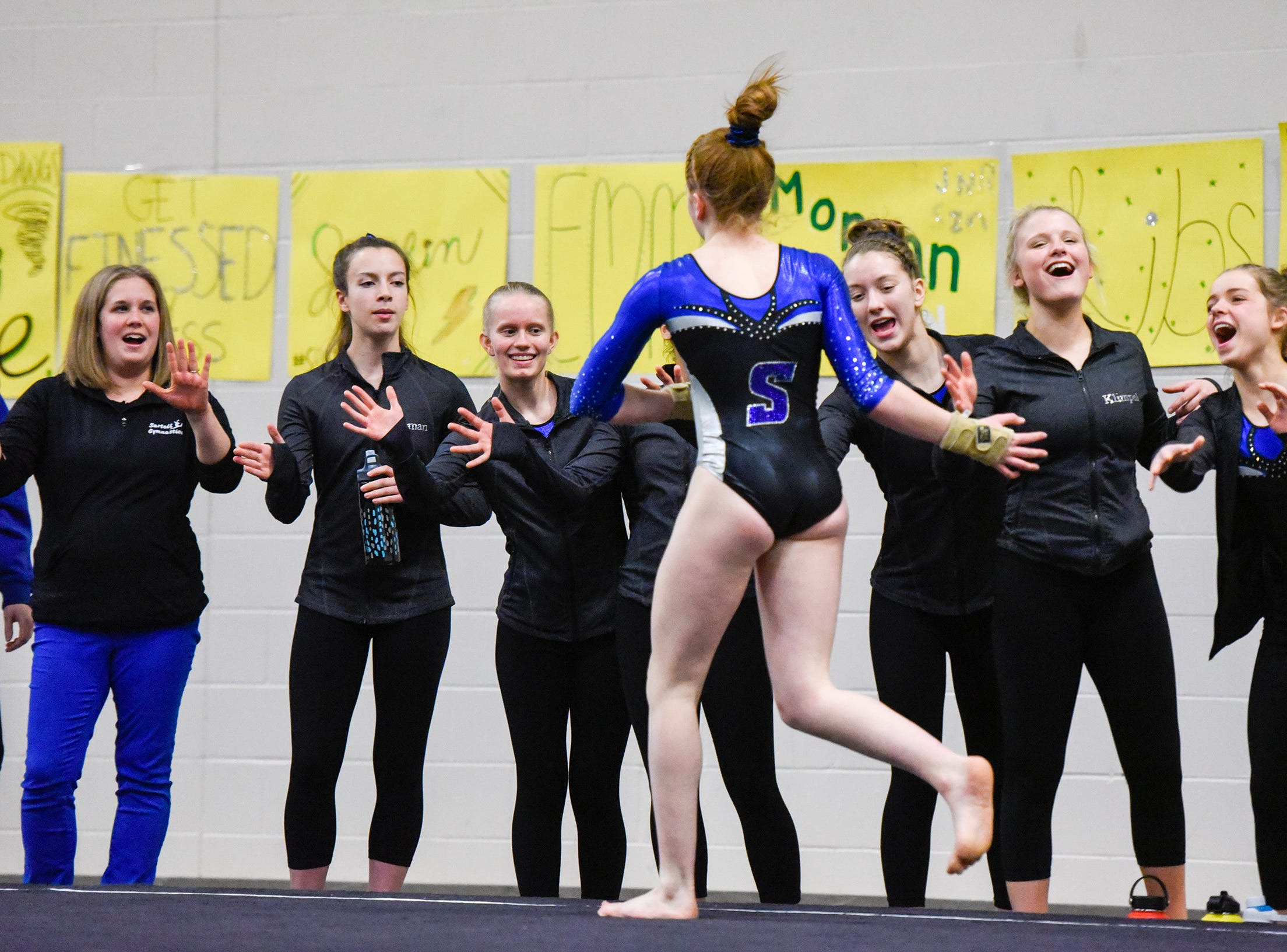 Sartell's Marlys Michaud is met by teammates after her floor routine Thursday, Jan. 3, at the Sauk Rapids-Rice High School.