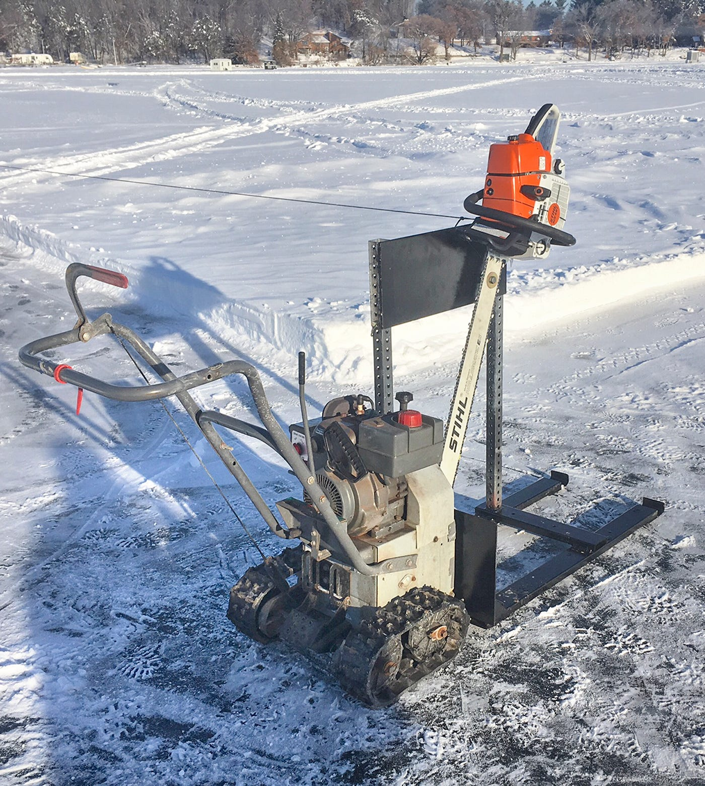 A homemade machine used to carve ice is made using pieces from a snowblower, steel skis and a saw that slides up and down.