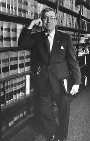 George Langford by bookcase at Municipal Corp, Jan. 19, 1984.