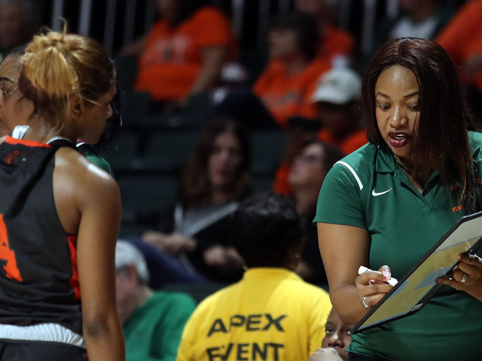 FAMU associate head coach LaTasha Shipman-Ganus goes over sets with 	Deja Antoine against the Hurricanes in the Miami Holiday Classic.