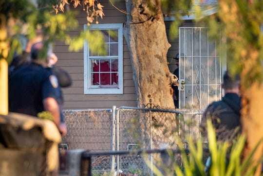 Abiel Innis De Joel Rios appears briefly as Visalia Police officers surround a house in the 200 block of N.E. 4th Street after a shooting at the home on Thursday, January 3, 2019. Rios, a suspect in the shooting, was shot by officers after repeated attempts to resolve the issue peacefully.