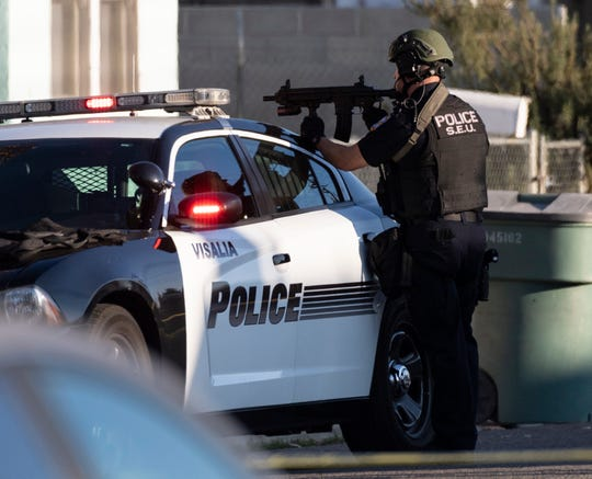 Visalia Police SWAT officers surround a house in the 200 block of N.E. 4th Street on Thursday, January 3, 2019. Joel Abel Rios was suspected of shooting his brother and refused to surrender to police for hours.