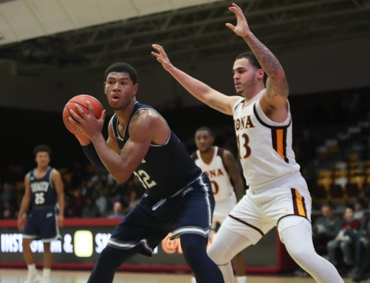 Monmouth center Diago Quinn (32) works the ball under the basket as Iona forward Jahnathan Maxwell (13) defends during the MAAC league men's basketball game at the Hynes Center at Iona College in New Rochelle on Thursday, January 3, 2019.