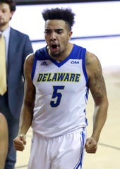 Delaware's Eric Carter lets out a whoop as he heads for the locker room after the Blue Hens' 58-56 win at the Bob Carpenter Center Thursday.