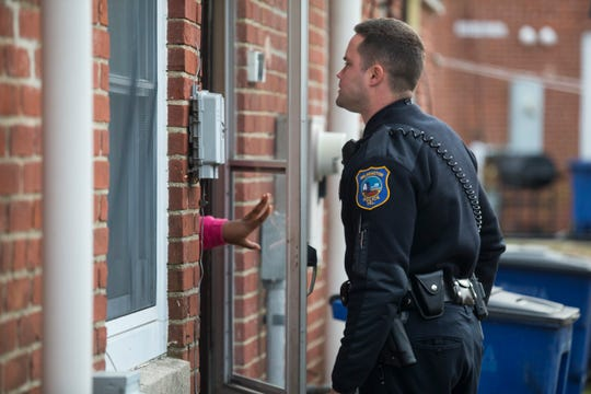 A member of the Wilmington Police Department speaks to a   neighbor where a suspected burglary took place Wednesday, Dec. 5, 2018 in Wilmington.