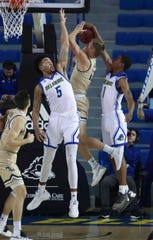 Delaware's Eric Carter (5) and Kevin Anderson defend a shot by William and Mary's Luke Loewe in the first half at the Bob Carpenter Center Thursday.