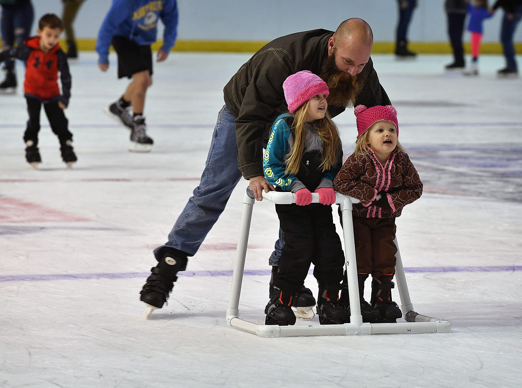 Curtis Hoskins pushes his daughters, Sadie, left, and Piper, around  the ice at Kay Yeager Coliseum Friday afternoon during the last Open Skate event of the season.