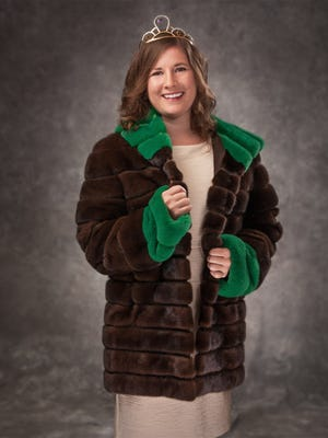 Alice in Dairyland Kaitlyn Riley wears a mahogany mink paired with white mink dyed green on the plush hood and sleeve cuffs, donated by Zimbal Mink of Sheboygan Falls.