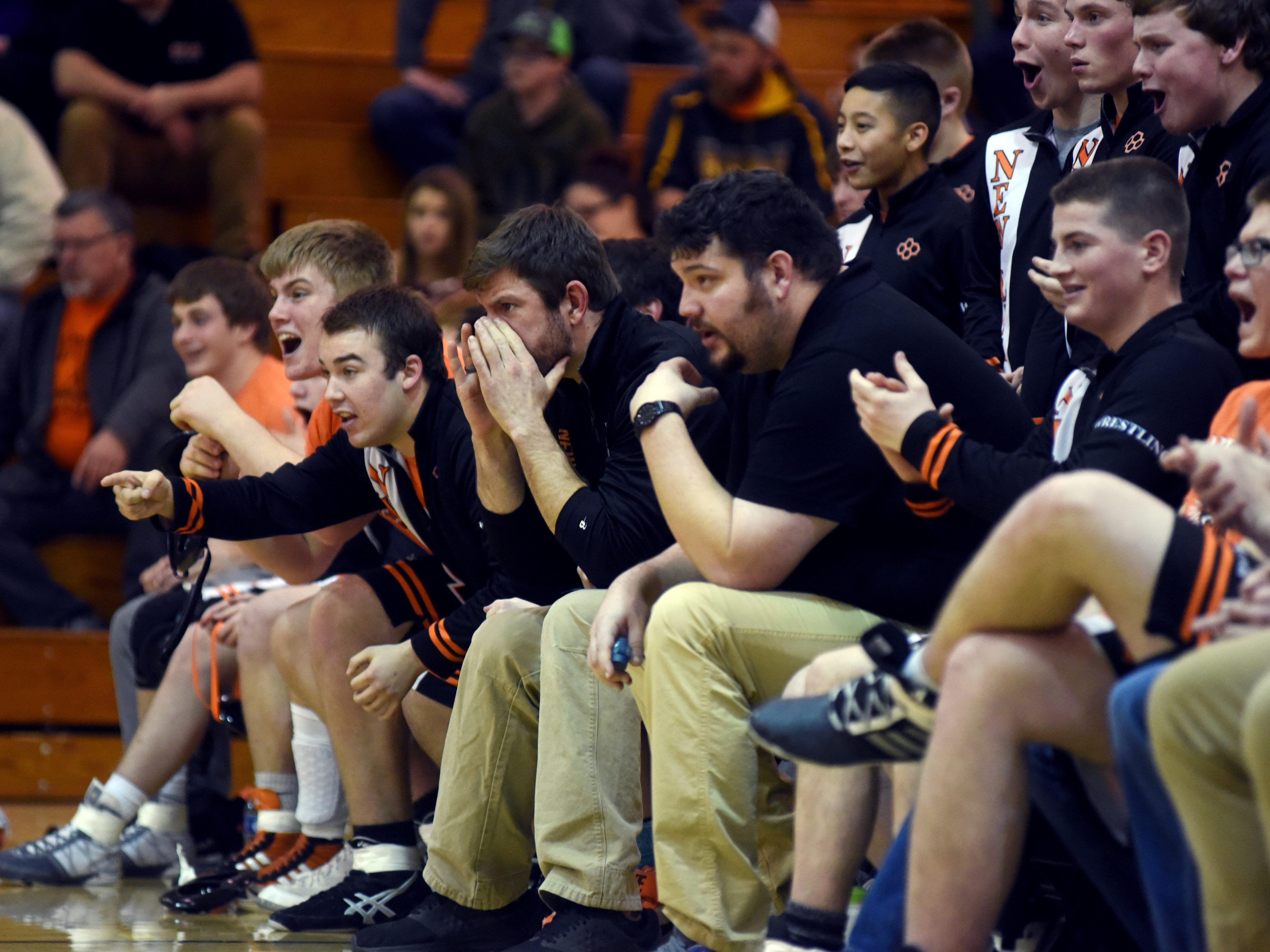 New Lexington coaches and wrestlers watch the action against Tri-Valley.