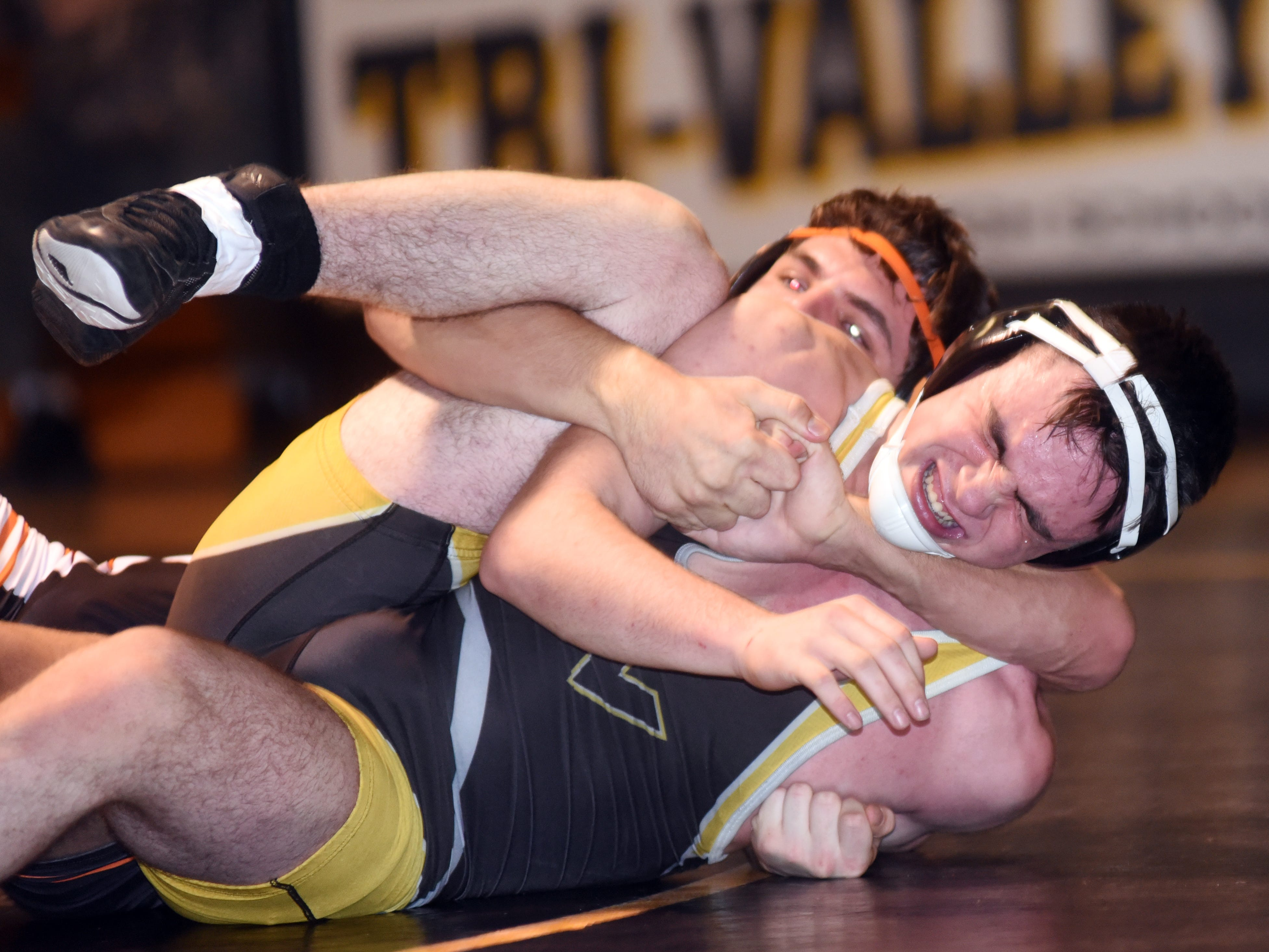 Tri-Valley's Porter Blackmond tries to fight out of a cradle from New Lexington's Layne Talbot at 170 pounds.