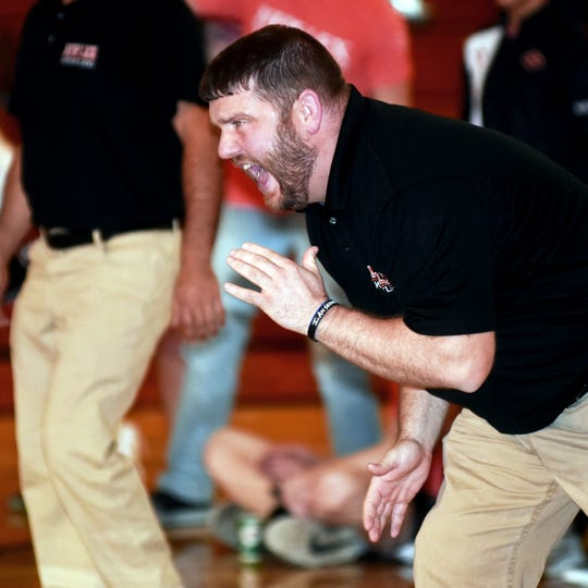 New Lexington coach David Ratliff yells out instructions to one of his wrestlers during the Panthers' 42-31 win against Tri-Valley on Thursday in Dresden.