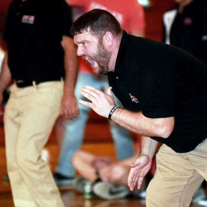 New Lexington coach David Ratliff yells out instructions to to one of his wrestlers during the Panthers' 42-31 win against Tri-Valley on Thursday in Dresden.
