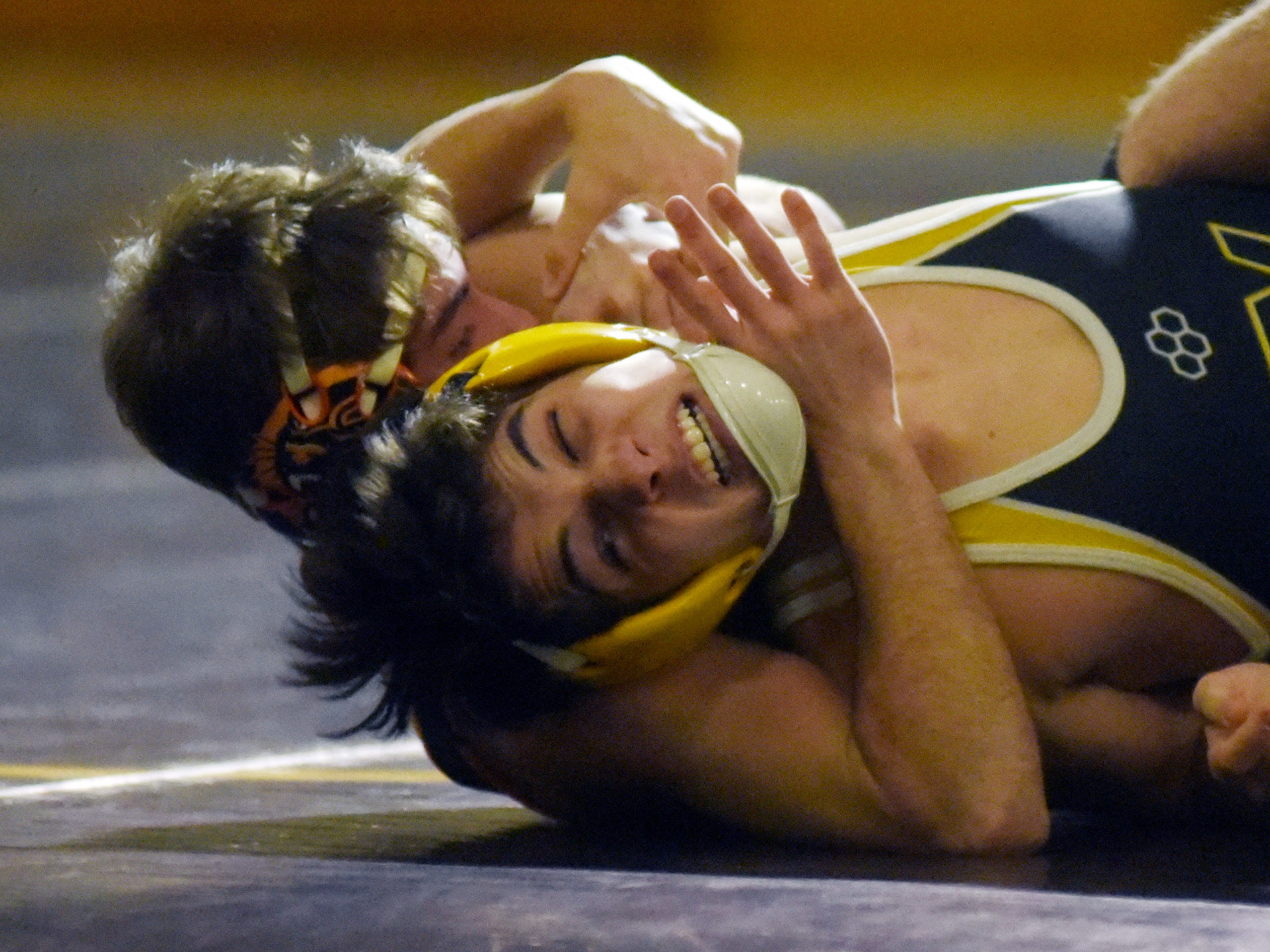 New Lexington's Blake Sheppard holds down Tri-Valley's Garrett Folden.