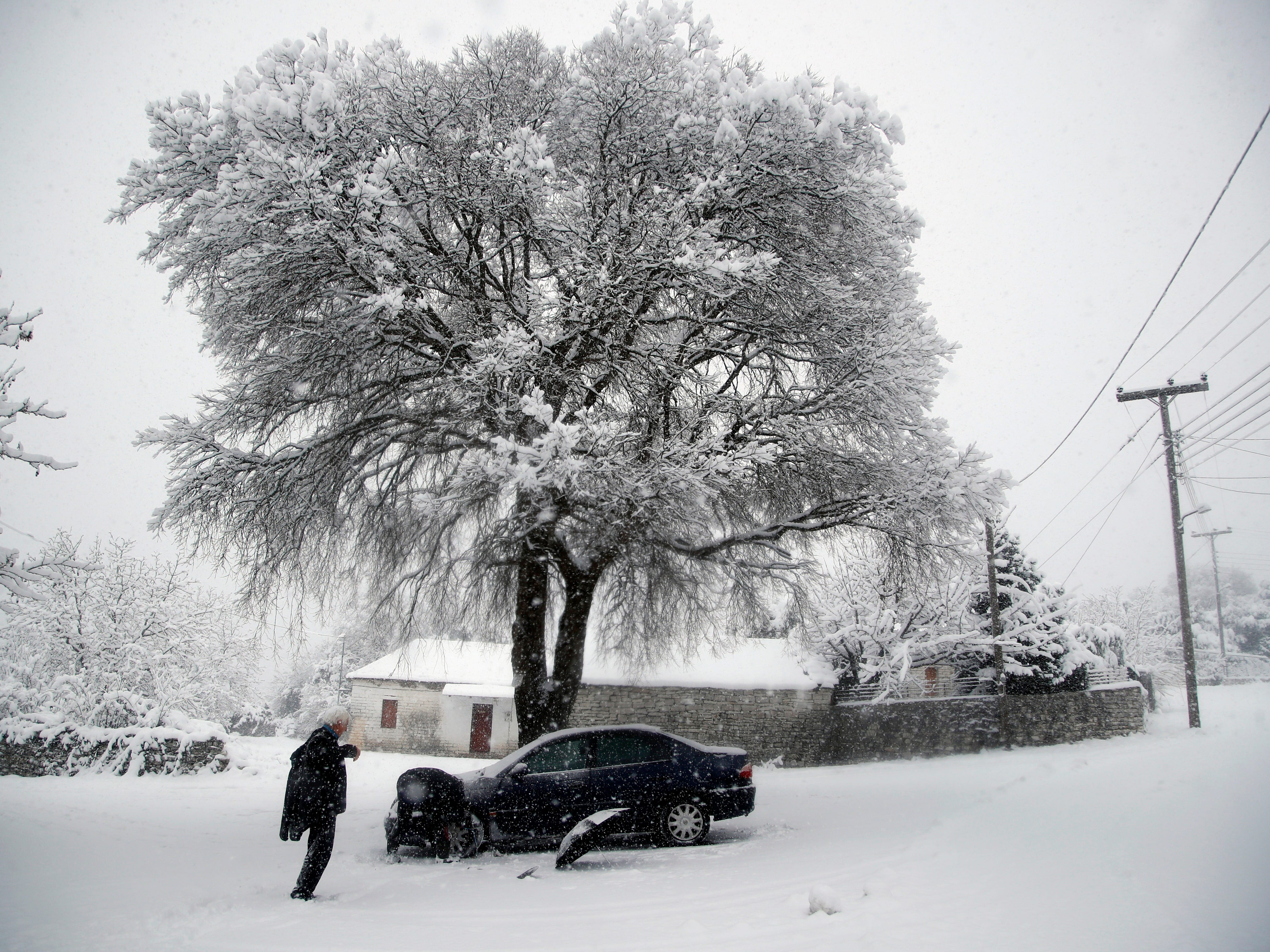 Two local residents try to put anti-skid chains on a car during a snowfall in Myrodafni village, near Ioannina city, northwestern Greece,  Jan. 4, 2019.