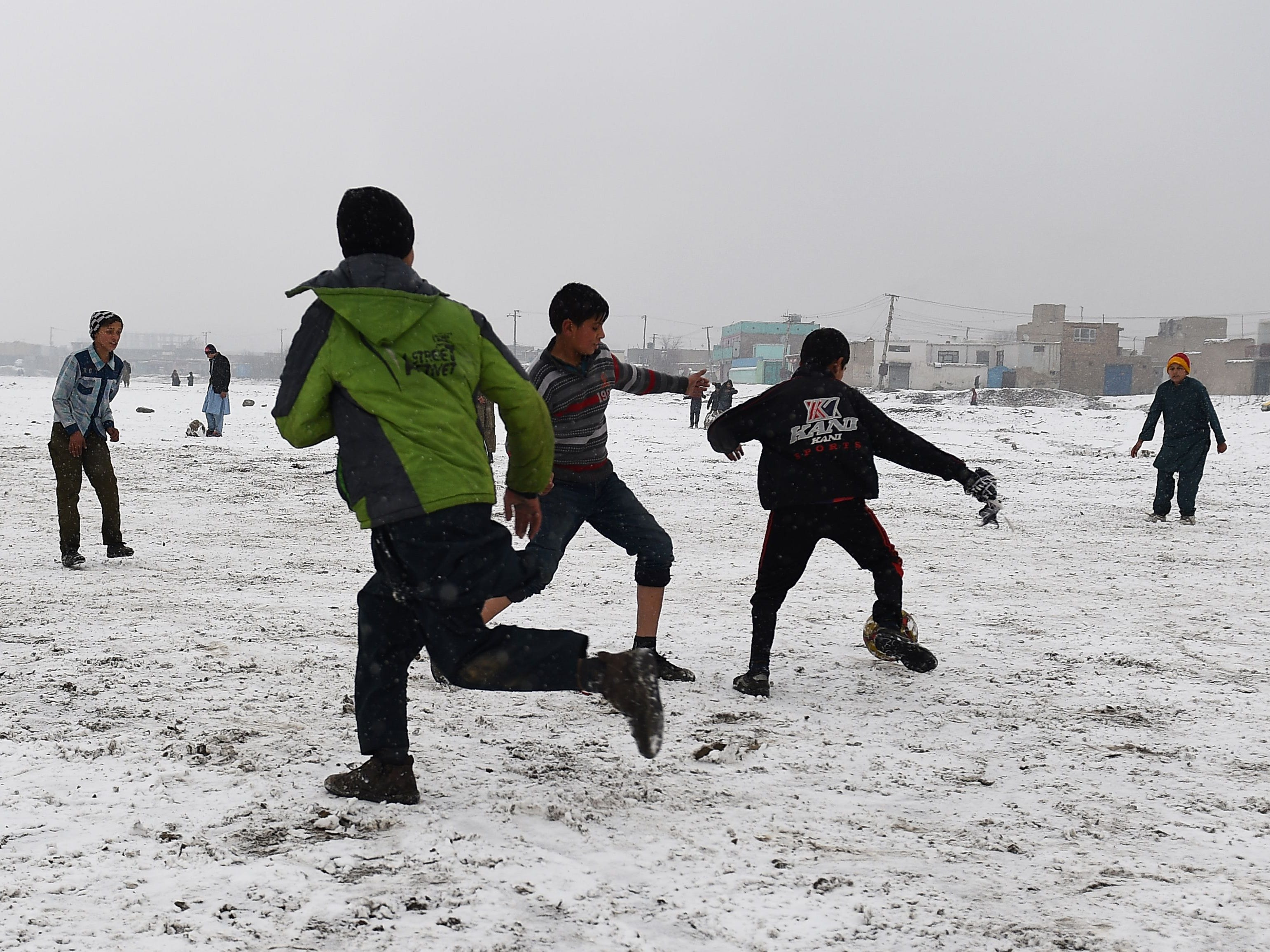 Afghan youths play football in the snow at Shuhada Lake in Kabul Jan. 4, 2019.