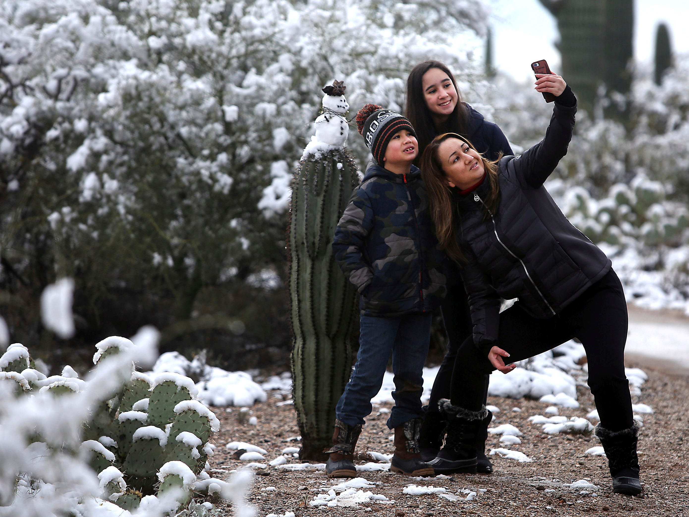 """It's the first time we've seen snow the desert,"" says Mayra Vasquez who brought Valeria Luzania, 11, and MarcoDario Luzania, 8, to Saguaro National Park East in Tucson Jan. 2, 2019. The kids built a snowman and the trio took a selfie with their creation. Parts of the Old Pueblo woke up to snow on New Year's Day."