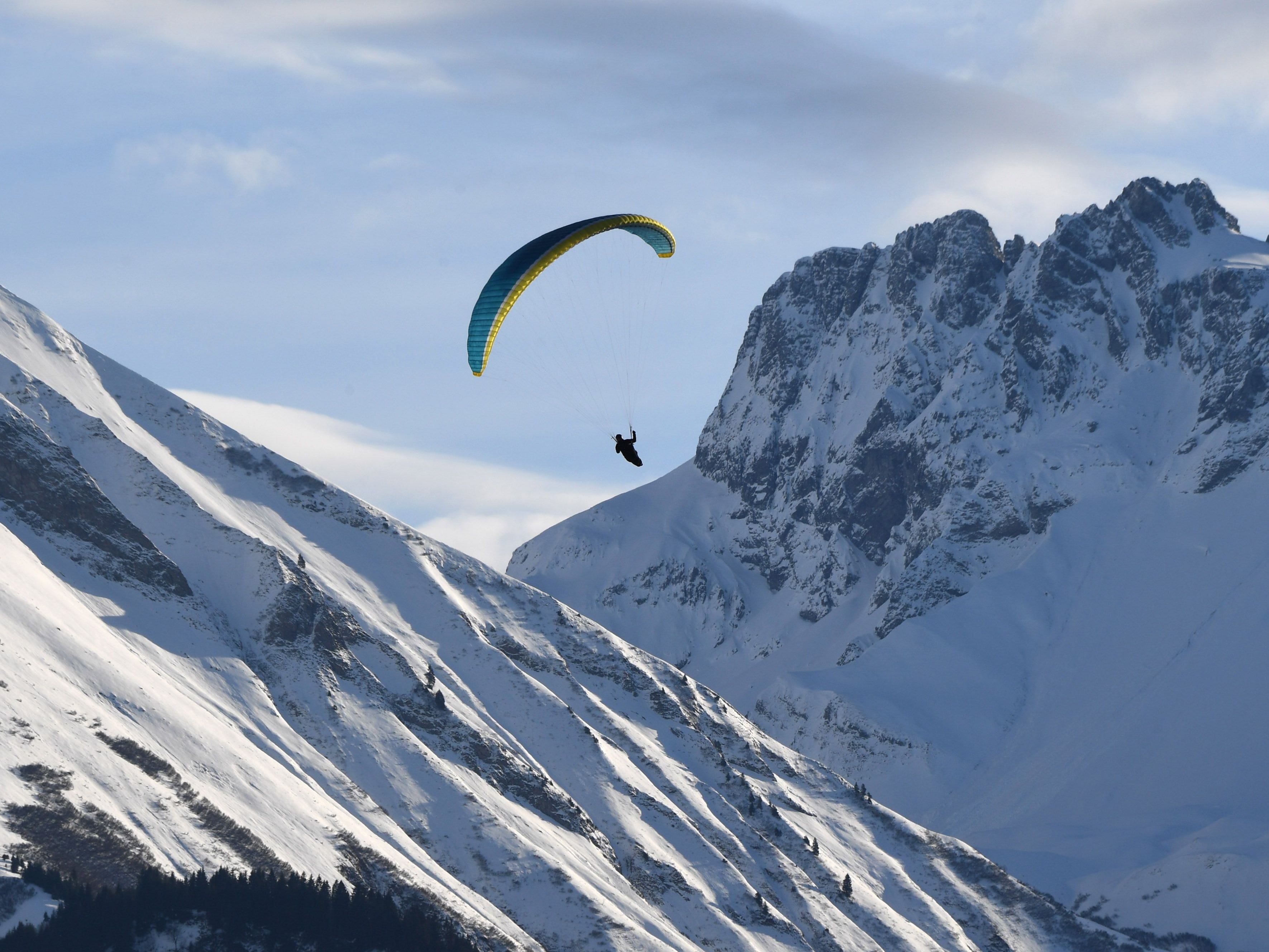A paraglider flies over the snow-covered Alp mountains near the Bavarian winter sport village Oberstdorf, southern Germany, Dec. 28, 2018.