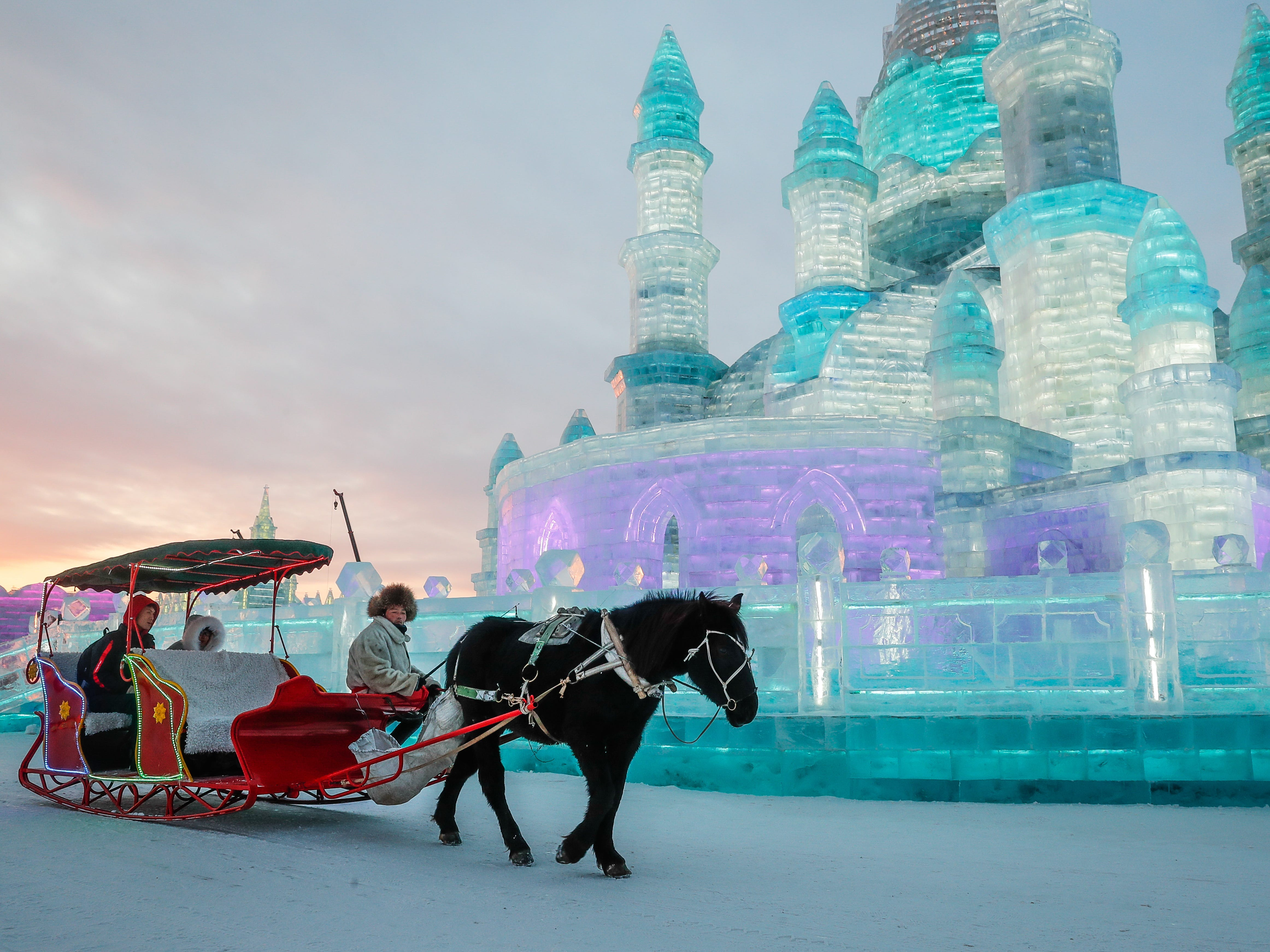 Visitors sit in a horse-drawn carriage in front of the ice sculptures at the Ice and Snow World during the annual Harbin International Ice and Snow Sculpture Festival, in Harbin, China.