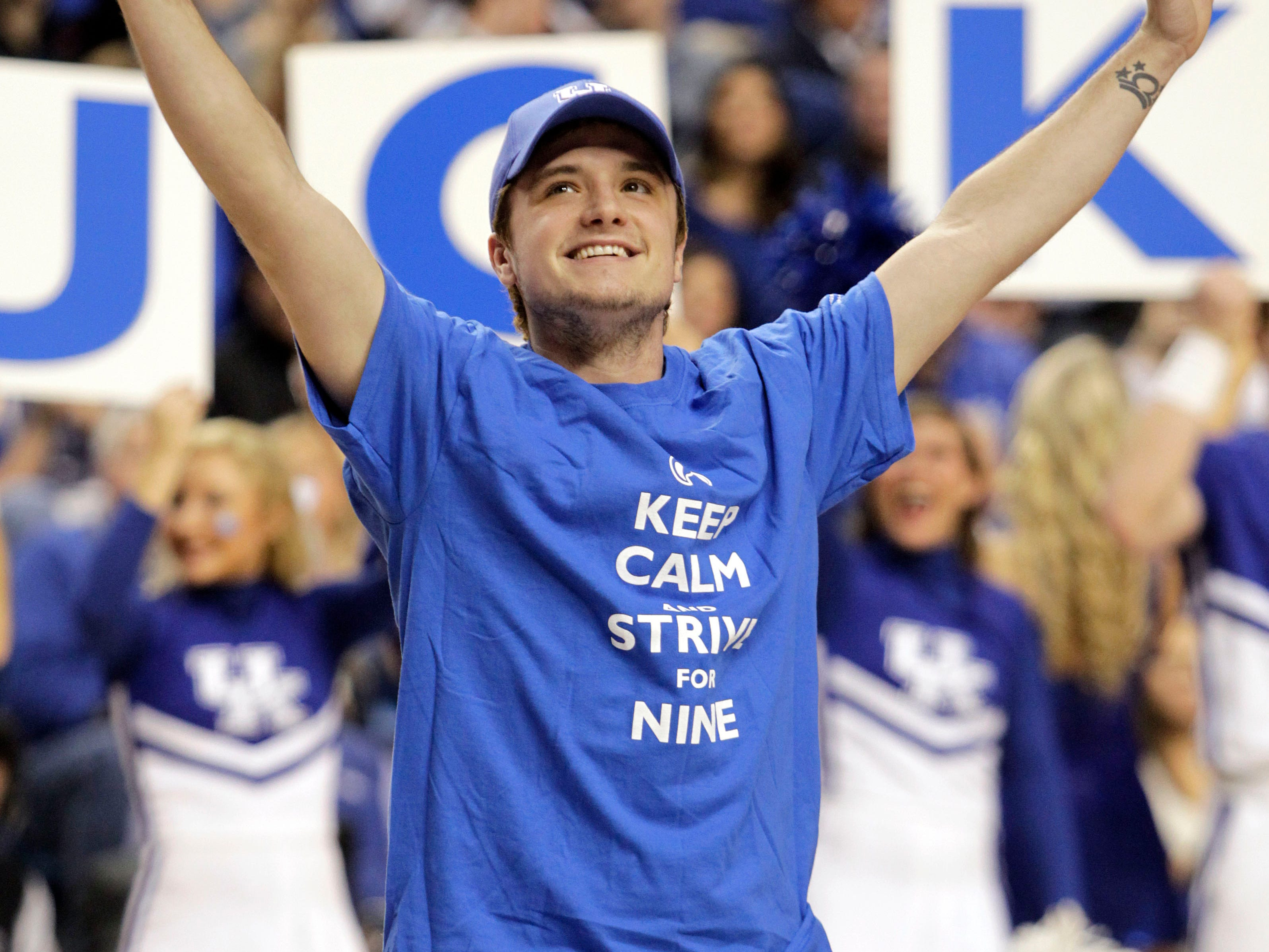 """Josh Hutcherson, Kentucky native and one of the stars of the film """"The Hunger Games,"""" salutes the crowd during the second half of an NCAA college basketball game between Kentucky and  Louisville, Saturday, Dec. 28, 2013, in Lexington, Ky. Kentucky won 73-66. (AP Photo/James Crisp) ORG XMIT: KYJC110"""