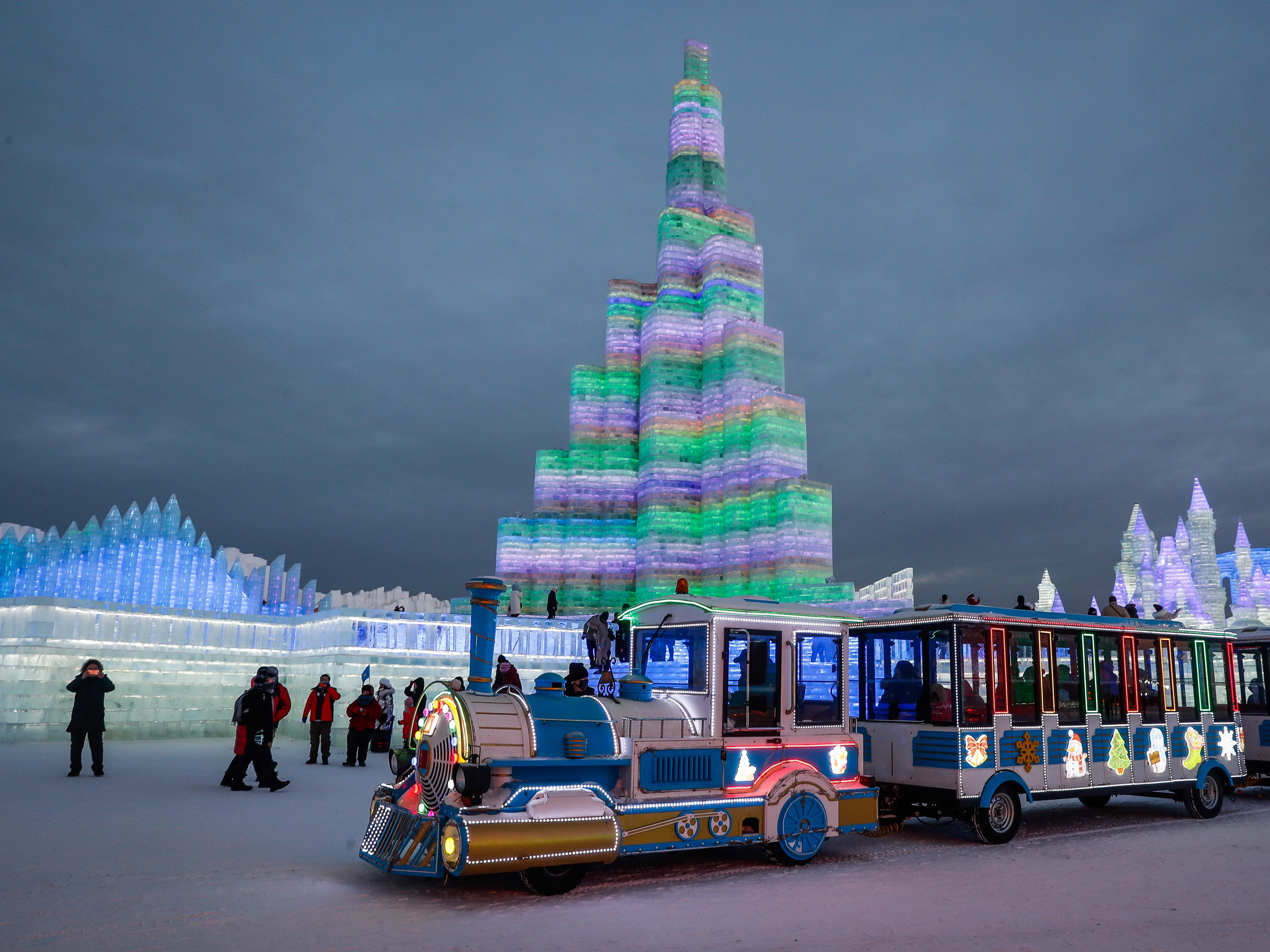 People visit ice sculptures illuminated by colored lights.