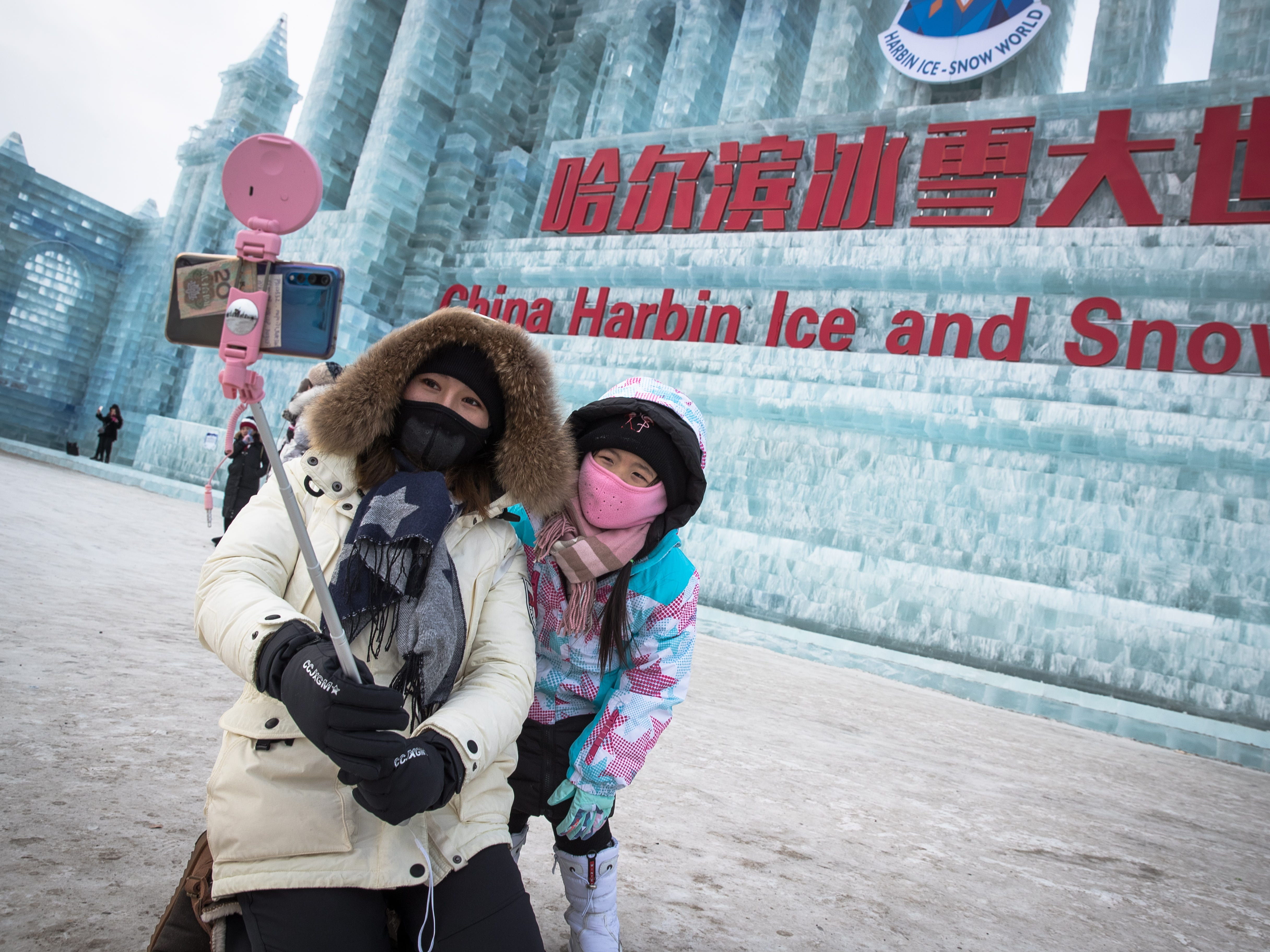 These two take a selfi in front of the ice sculptures.