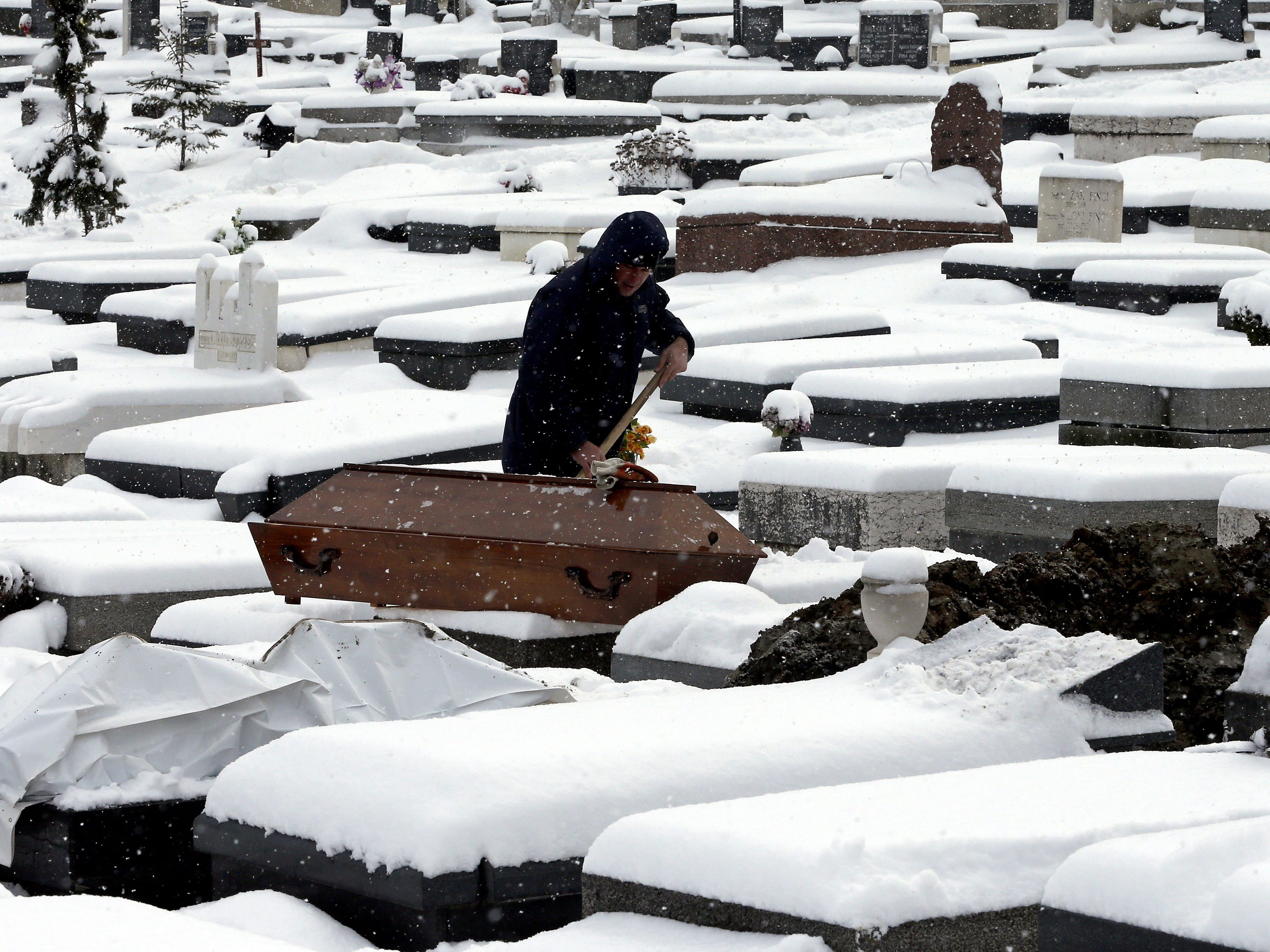 A grave digger works at the cemetery prior to a funeral in Sarajevo, Bosnia and Herzegovina, Jan. 3,  2019,